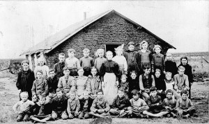 teacher and students in front of sod schoolhouse
