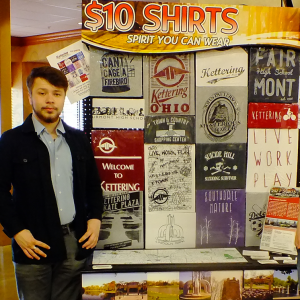 Spencer Wolf showcases t-shirts he helped design as part of a CTE project.