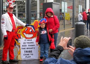 A mother and son pose before a Chief Wahoo sign at the Indians' season opener this year.